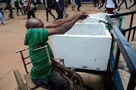 """رجل في كرسي متحرك يغسل يديه في مغسلة عامة في نيروبي، كينيا، 22 مارس/آذار 2020، اتباعا للتعليمات الصحية من السلطات في إطار مكافحة انتشار فيروس """"كورونا"""". إلا أنه يصعب عليه اتباع هذه الممارسة الأساسية بسبب إعاقته. © 2020 دنيس سيغوي/سيبا عبر أسوشيتد برس"""